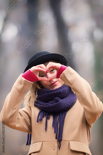 Plakát Cute smiley girl holding a heart - shape.