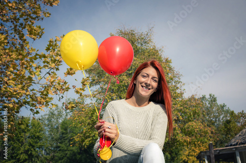 Happy redhead woman with balloons in the park.