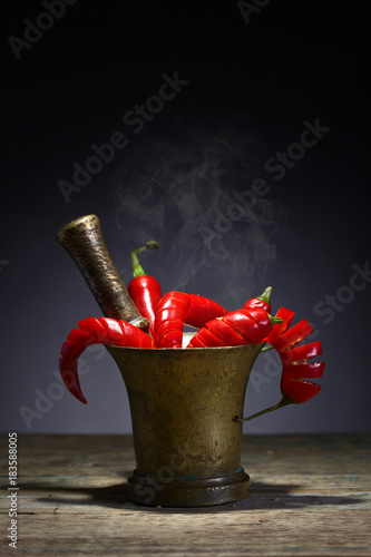 Tuinposter Hot chili peppers Red chili pepper in old copper mortar.