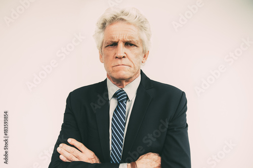 Portrait of displeased senior businessman in suit