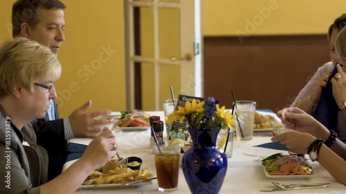 Tight shot of business people at a luncheon at a restaurant with flowers on the table each salads and soup.