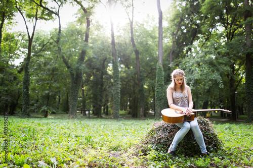 Fotobehang Muziek Heartbroken woman in nature with guitar