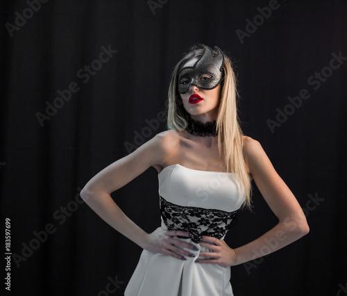 Mystic blonde woman in mask on dark background