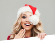 Cheerful Model Christmas Woman with White Banner Background with Empty Copy space. Happy Girl in Santa Hat, Winter Woman Christmas Concept