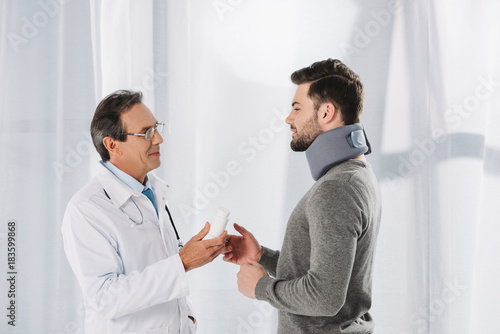 doctor giving pills to patient in neck brace