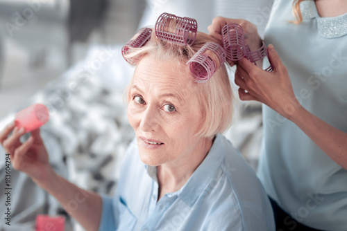 Plexiglas Kapsalon New hairstyle. Pleasant nice elderly woman wearing hair rollers and looking at you while waiting for her new hairstyle to be done