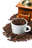 cup with coffee beans and handmilled coffee grinder on white background, vertical - 183617255