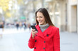 Lady using a smart phone on the street in winter - 183617400