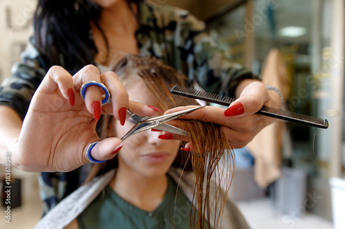 Foto op Canvas Kapsalon Working day inside the hair salon, hairdresser makes hair cut on young woman.