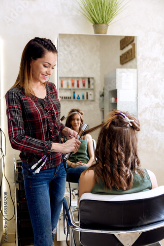 Fototapeta Working day inside the hair salon, hairdresser making hairstyle on young woman with hair straightener.