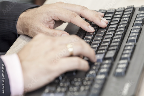 Poster close-up hands of man on computer keyboard