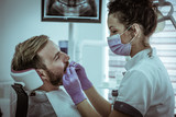 Female dentists operate patient. - 183630602