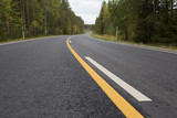 Brand new asphalt road in autumn day. Yellow lines. - 183632236