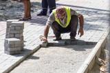 Worker puts sidewalk tile on the road - 183638449