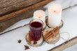 mulled wine on a wooden stand white candles bundle of dry cinnamon sticks on the table with the snow