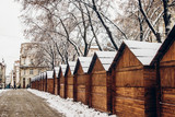 wooden cabins in snow for christmas market. snowy town square in Lviv. european city preparing for winter christmas holidays, space for text - 183643035