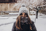 stylish hipster woman in knitted hat standing in snowy city street. beautiful fashionable girl in warm clothes in cold weather with wind. space for text - 183643081