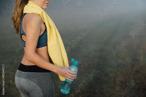 Woman in sport pants holding a bottle of water