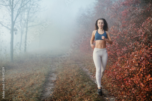 Woman jogging in the foggy autumn morning