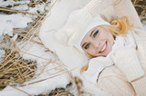 Portrait of a girl lying on snow covered dry grass 9161. - 183651412