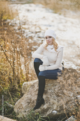 Beautiful girl resting on a huge stone on a background of a winter road 91
