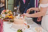 The young husband and wife to divide pieces of cake to treat your guests - 183651851