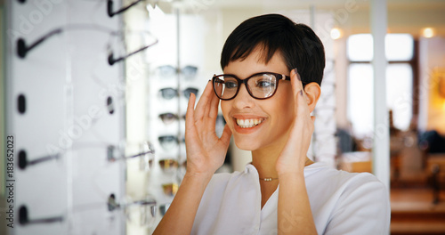 canvas print picture Beautiful woman with optician trying eyeglasses