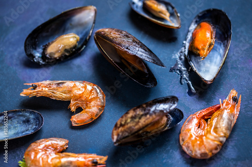Fototapeta Seafood mussels in the shell and shrimp on a blue background grill