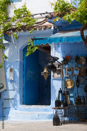 Traditional moroccan courtyard in Chefchaouen blue city medina in Morocco, architectural details in Blue town Chaouen. Typical blue walls and colorful flower pots. © sefoma