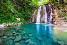 Waterfall in a green spring forest surrounded by stones, clear turquoise water on an impressive natural landscape. 33 Waterfalls, Sochi, Russia.
