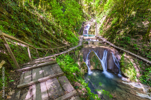 Waterfall in a green spring forest surrounded by a ladder railing and railing, summer natural landscape. 33 Waterfalls, Sochi, Russia. - 183659210