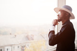 Rich african man looking at panoramic window at his penthouse. Portrait of successful black man in hat indoor. - 183663063
