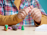 Boy is sculpting with colorful modelling clay. Close up. - 183663884