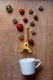cup on lying on side with Eiffel tower toy and Christmas baubles