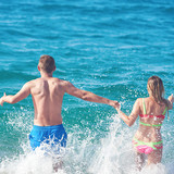 Caucasian couple running into the sea water. Back view. - 183664020