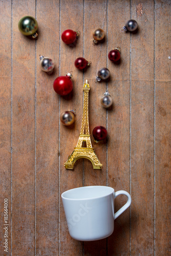 Fotobehang Eiffeltoren cup on lying on side with Eiffel tower toy and Christmas baubles
