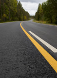 Low point of view on new asphalt road, curves ahead. White and yellow marks. - 183668469