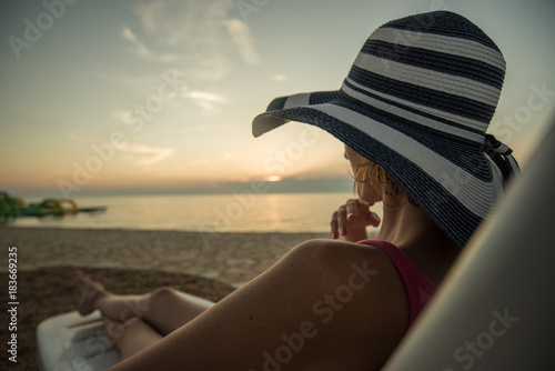 Sticker Single woman looking at sunset sitting on a chair