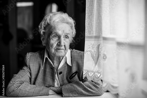 Old lady sadly sitting near the window. Poster