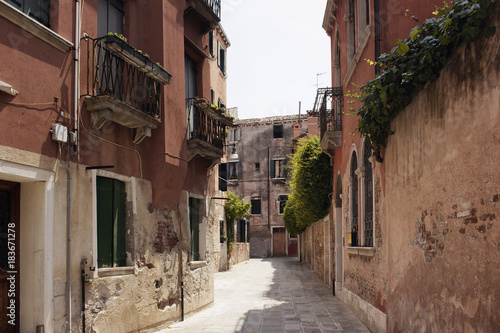 Staande foto Smal steegje View of a narrow street with old, historical buildings in Venice