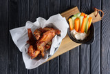 Snack for beer. Spicy chicken wings with fresh carrot and celery and sauce - 183672061