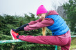 Woman wearing sportswear exercising outside during autumn - 183672853