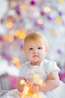 Beautiful little baby celebrates Christmas. New Year's holidays. Sweet baby girl in cute dress having fun in festive decorated room.