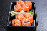 Spicy salmon makizushi roll with salmon in take-away container over slate plate background - 183683676