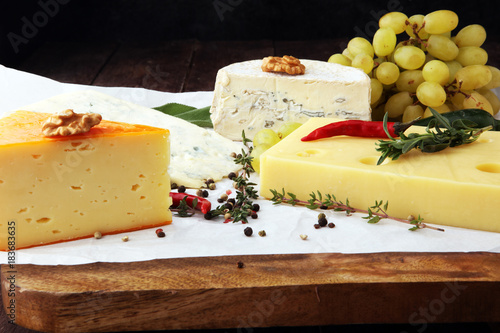 Fototapeta Different types of cheeses on board with walnut and grapes.