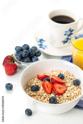 Wall mural Bowl of Oats with Berry Toppings, Cup of Blueberries, and Cup of