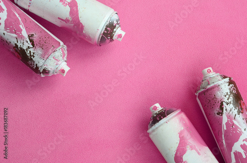 Some used pink aerosol spray cans with paint drips lies on a blanket of soft and furry light pink fleece fabric. Classic female design color. Graffiti hooliganism concept - 183687092
