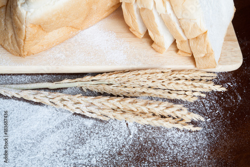 Bread with wheat ears on dark board with flour