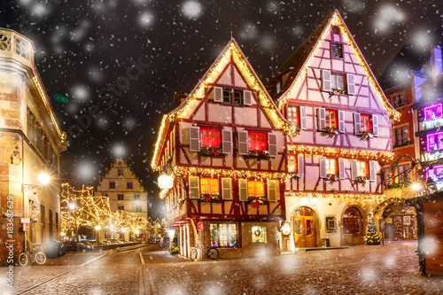 Traditional Alsatian half-timbered houses in old town of Colmar, decorated and illuminated at snowy christmas night, Alsace, France