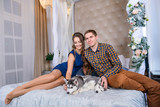 Beautiful young couple in the New Year atmosphere with puppies of the Husky - 183690843